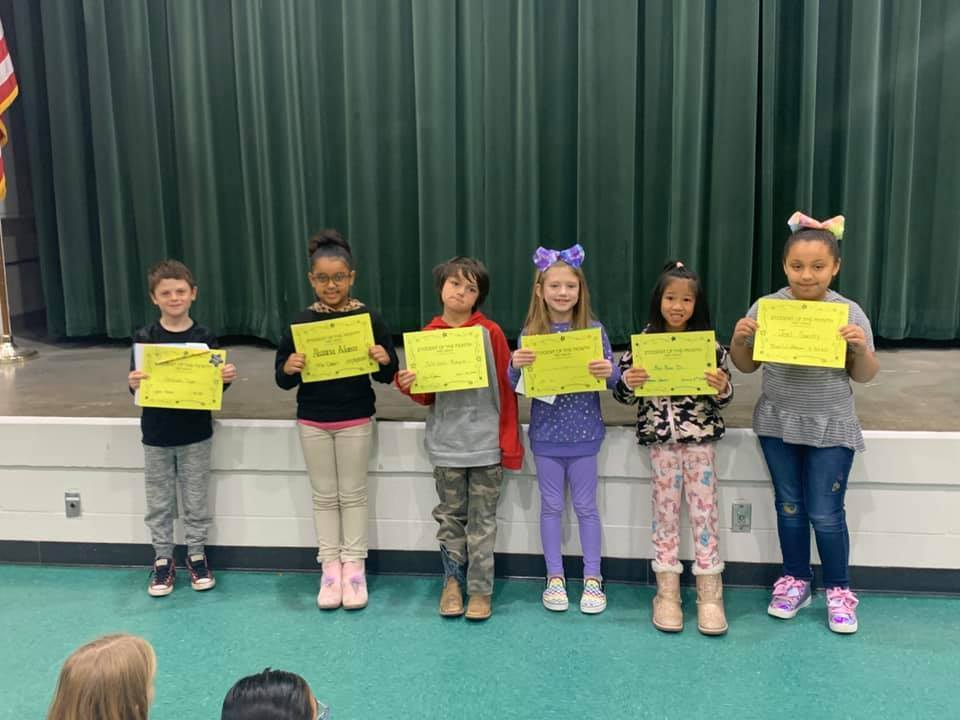 6 first grade students hold their student of the month certificates.