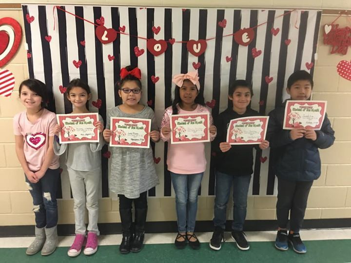 2nd Grade Students of the Month hold up their certificates.